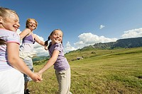 Italy, Seiseralm, Mother and children 6_7, 8_9 dancing in meadow, laughing, portrait