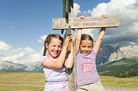 Italy, Seiseralm, Girls 6_7, 8_9 standing by sign post, smiling, portrait