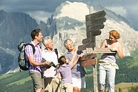 Italy, Seiseralm Family standing next sign post
