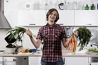 Germany, Berlin, Young man in kitchen holding bunch of carrots and spring onions, laughing, portrait (thumbnail)