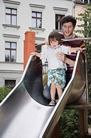 Germany, Berlin, Father helping son 3_4 on shute at playground