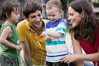 Germany, Berlin, Parents looking at ladybird on childs 2_3 arm, laughing, portrait