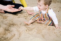 Germany, Berlin, Family and son 2_3 in sandbox, side view, portrait