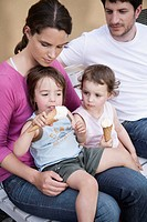 Germany, Berlin, Family sitting on bench, children 3_4 eating icecream, portrait