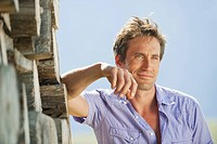 Italy, South Tyrol, Man leaning against pile of wood, portrait, close_up