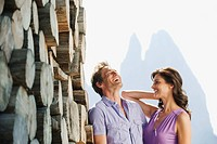 Italy, South Tyrol, Seiseralm, Couple standing next pile of wood, portrait