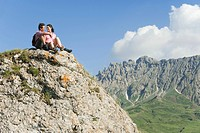 Italy, South Tyrol, Couple sitting on rock, taking a break