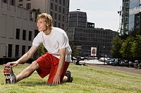 Germany, Berlin, Young man stretching on lawn