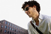 Germany, Berlin, Young man listening to MP3_Player