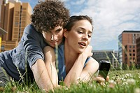 Germany, Berlin, Young couple lying in meadow, woman holding mobile phone, portrait, close_up