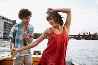 Germany, Berlin, Young couple on motorboat, man looking at woman dancing, portrait