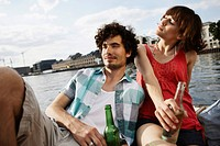 Germany, Berlin, Young couple on motor boat, holding bottles, portrait, close_up