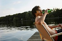 Germany, Berlin, Young man drinking bottled beverage, side view, portrait