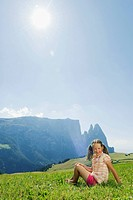 Italy, South Tyrol, Seiseralm, Girl 6_7 sitting in meadow