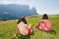 Italy, South Tyrol, Seiseralm, Two girls 6_7 10_11 sitting in meadow, rear view