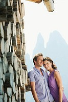 Italy, South Tyrol, Seiseralm, Couple leaning against pile of wood pile, portrait