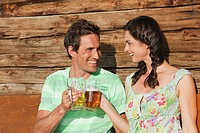 Italy, South Tyrol, Couple toasting with beer, laughing, portrait