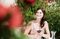 Italy, South Tyrol, Woman in garden holding a glass of red wine, looking away