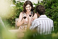 Italy, South Tyrol, Couple in restaurant holding glasses of red wine