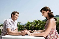Italy, South Tyrol, Couple in restaurant holding hands