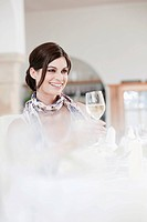 Woman in restaurant holding glass of white wine, smiling, portrait