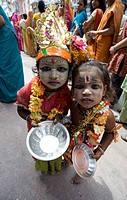 Two street children dressed in the style of Krishna at Diwali festival time, begging for alms from temple visitors, Udaipur, Rajasthan, India, Asia
