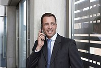 Germany, Cologne, Businessman leaning against wall using mobile phone, smiling, portrait