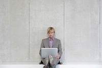 Germany, Cologne, Businessman leaning against wall, using laptop