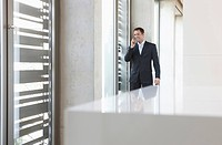 Germany, Cologne, Businessman in corridor using mobile phone