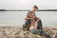 Germany, Berlin, Lake Wannsee, Young couple sitting on lakeshore, portrait
