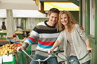 Germany, Bavaria, Munich, Couple with bicycles at Viktualienmarkt