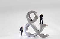 Business men figurines next Ampersand sign