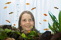 Girl 8_9 watching fish, view through fish tank