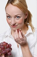 Young woman holding grapes, smiling, portrait