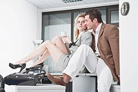 Germany, Business people in office, sitting on desk, flirting