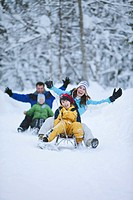 Germany, Bavaria, Family sledding, having fun