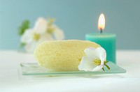 Sponge on glass platter, cherry blossom and burning candle