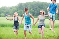 Germany, Bavaria, Young people running across meadow