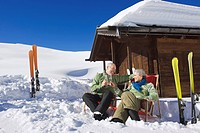 Italy, South Tyrol, Seiseralm, Senior couple sitting in front of log cabin, holding champagne glasses