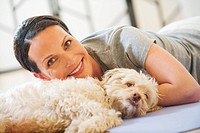 Woman lying on floor with dog beside her, smiling, portrait