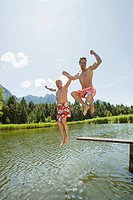 Italy, South Tyrol, Men jumping into lake, fooling about