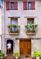 Man with a wicker shopping basket leaves medieval French house in St Sauveur sur Tinee, Alpes Maritimes, Provence, France