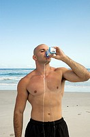 Muscle man drinking milk from carton on the beach
