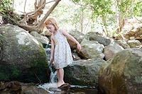 Girl standing on rock in river