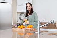 Young woman with oranges and orange juice (thumbnail)