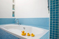 Rubber ducks on side of bath
