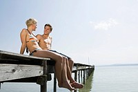Germany, Bavaria, Ammersee, Young couple relaxing on jetty