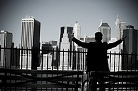 Man with arms open and view of lower manhattan