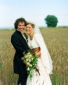 Scandinavia, Sweden, Oland, Bride and groom standing in field, smiling, portrait