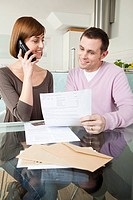 Couple on telephone with bills